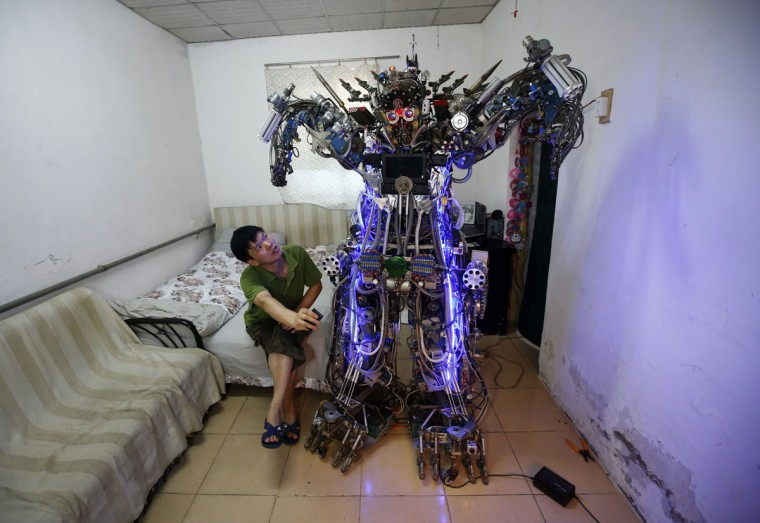 """Chinese inventor Tao Xiangli controls his home-made humanoid robot with a remote controller as he poses with it during a photo opportunity at his house located in a old residential area in Beijing on Aug. 8, 2013. The self-taught Chinese inventor built the home-made robot, named """"The King of Innovation"""", out of scrap metal and electronic wires that he bought from a second-hand market. Tao completed his creation in less than a year, with costs of production and living expenses amounting to 300,000 yuan ($49,037). However, the robot, which measures 2.1 meters (6.9 feet) in height and 480 kg (1058 lbs) in weight, turned out to be too tall and heavy to walk out of the front door of his house. It can perform simple movements with its hands and legs and also mimic human voices. (REUTERS/Kim Kyung-Hoon)"""