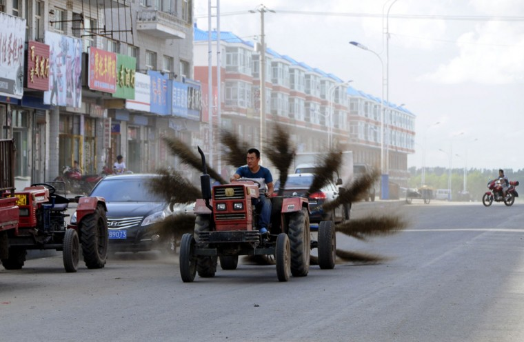 A man drives an improvised tractor with 12 brooms tied in the rear, as he tries to clean a road in Mohe, Heilongjiang province, on Aug. 31, 2013. (Reuters photo)