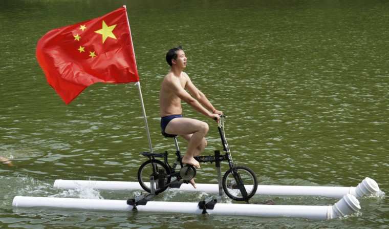 A Chinese flag is seen as Liu Wanyong performs on his invention, an improvised bicycle which is held afloat by plastic tubes, in Zhenning, Guizhou province, on Aug. 29, 2013. (Reuters photo)