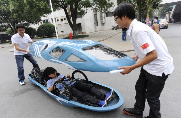 Students open the top of a newly made fuel-efficient vehicle on a street inside Hunan University after a test drive in Changsha, Hunan province on Oct. 8, 2013. A group of students at Hunan University designed and made the 2.85-meter-long innovative vehicle, which travels up to a maximum speed of 60km/h (37m/h), in six months with the cost of about 50,000 yuan ($8,168). The fuel-efficient vehicle, which is about 50 kilogram (110 lb) in weight, is able to travel 100 kilometers (62 miles) with one liter of gasoline, according to local media. (REUTERS photo)