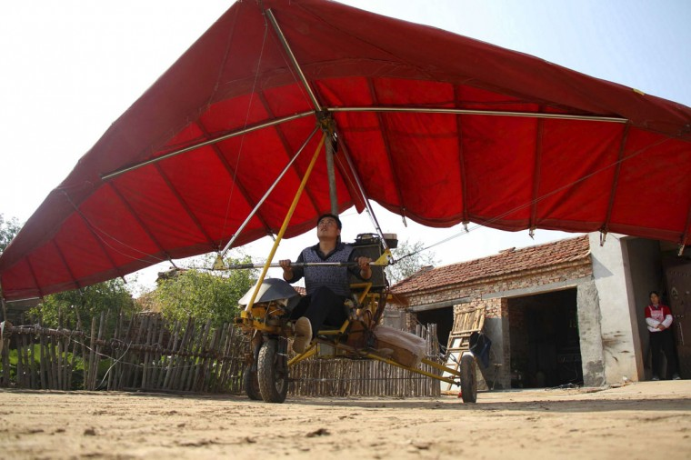 Zhang Haiyong adjusts his home-made plane in Binzhou, Shandong province, on Oct. 17, 2013. Zhang, 30, spent five months and more than 8,000 yuan ($1312.80) to build the plane made from steel bars, canvas and used car engines. During test flights, the plane was able to fly two to three meters above ground during, local media reported. (REUTERS/China Daily)
