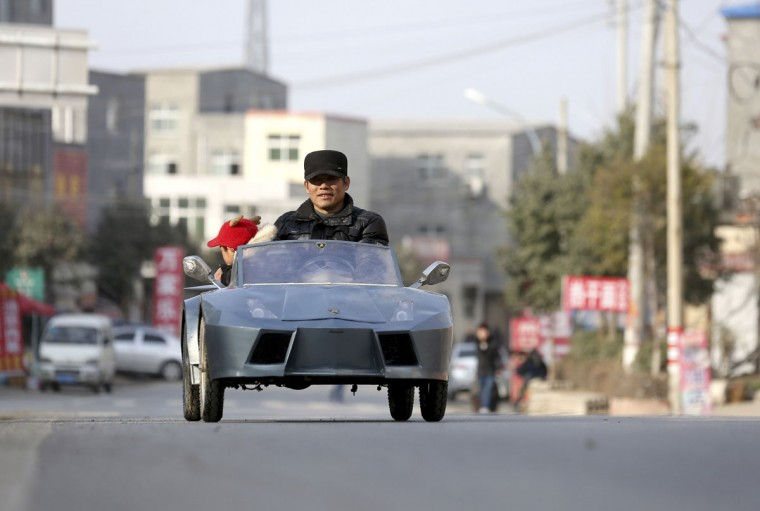 """Guo, a farmer in his 50s, drives his home-made scale replica of a Lamborghini with his grandson on a street in Zhengzhou, Henan province on Feb. 19, 2014. Guo spent 6 months and about 5,000 yuan (821 USD) to make the 2-metre-long, 1 meter-wide """"Lamborghini"""" as a toy for his grandson. The replica, mainly made of scrapped metals and parts from electricity bicycles, bears five sets of batteries and can travel as far as 60 km (37 miles) when fully charged, local media reported. (REUTERS/China Daily)"""