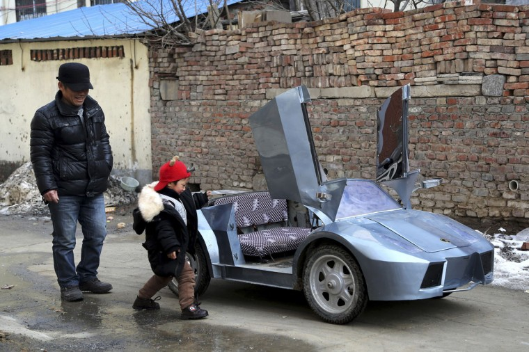 "Guo, a farmer in his 50s, looks on as his grandson gets on a scaled replica of a Lamborghini made by Guo, on a street in Zhengzhou, Henan province on Feb. 19, 2014. Guo spent 6 months and about 5,000 yuan (821 USD) to make the 2-meter-long, 1 meter-wide ""Lamborghini"" as a toy for his grandson. The replica, mainly made of scrapped metals and parts from electricity bicycles, bears five sets of batteries and can travel as far as 60 km (37 miles) when fully charged, local media reported. (REUTERS/China Daily)"