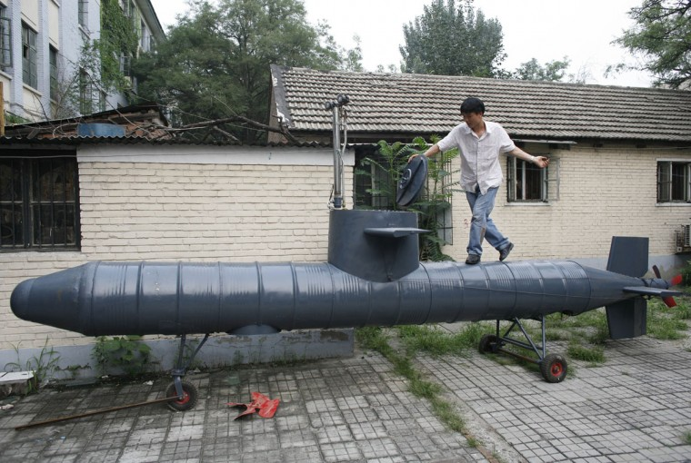 Tao Xiangli stands on his homemade submarine in a courtyard in Beijing on July 10, 2008. The amateur inventor says his submarine is made from old oil barrels but fully functional with a periscope, depth control tanks, electric motors and two propellers. (REUTERS/Reinhard Krause)