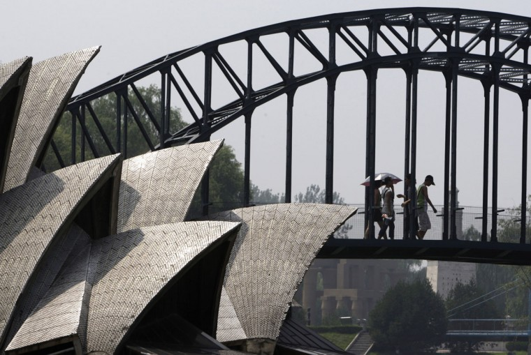 Visitors to Beijing's World Park walk across a replica of the Sydney Harbour Bridge situated next a replica of the Sydney Opera House in Beijing on July 16, 2008. (REUTERS/David Gray)
