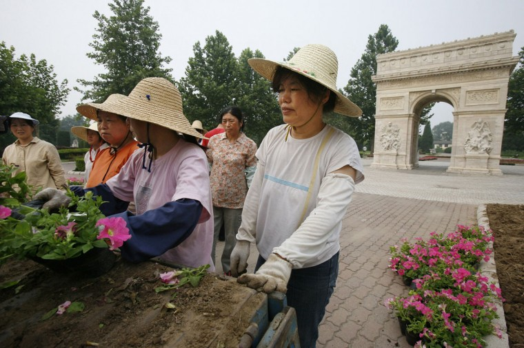 Workers unload flower pots near a replica of the Arc de Triomphe at Beijing World Park in Fengtai district, one of the three designated 'protest parks' in Beijing, on July 25, 2008. (REUTERS/Claro Cortes IV)