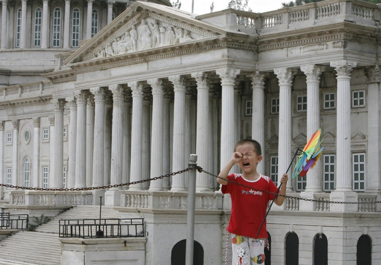 "A boy cries near a replica of the United States Capitol building at Beijing World Park, one of three designated ""protest parks"" in Beijing on July 25, 2008. (REUTERS/Claro Cortes IV)"