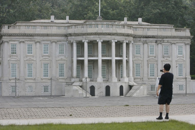 """A visitor takes photographs of a replica of the White House at Beijing World Park, one of the three designated """"protest parks"""" in Beijing, on July 25, 2008. (REUTERS/Claro Cortes IV)"""
