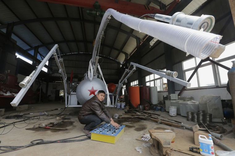 Zhang Wuyi looks up as he squats under a suction pipe of his new submarine that captures sea cucumbers at his workshop in Wuhan, Hubei province, March 25, 2013. Zhang, a 38-year-old local farmer who is interested in scientific inventions, has independently made eight miniature submarines with several fellow engineers, one of which was sold to a businessman in Dalian at a price of 100,000 yuan ($15,855) in 2011. The submarines, mainly designed for harvesting aquatic products, such as sea cucumber, have a diving depth of 20-30 metres (66-98 feet), and can travel for 10 hours, local media reported. (Reuters photo)