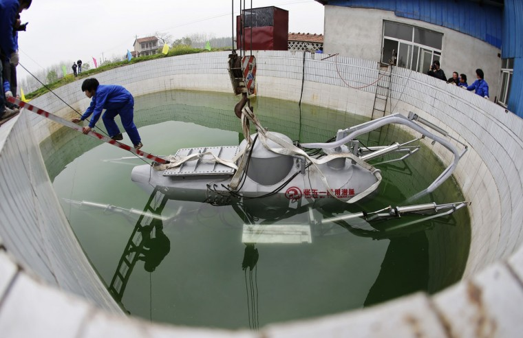 A worker climbs up from Zhang Wuyi's newly designed unmanned submarine that captures sea cucumbers, during a test operation at an artificial pool near a shipyard in Wuhan, Hubei province, March 26, 2013. Zhang, a 38-year-old local farmer who is interested in scientific inventions, has independently made eight miniature submarines with several fellow engineers, one of which was sold to a businessman in Dalian at a price of 100,000 yuan ($15,855) in 2011. The submarines, mainly designed for harvesting aquatic products, such as sea cucumber, have a diving depth of 20-30 metres (66-98 feet), and can travel for 10 hours, local media reported. (Reuters photo)