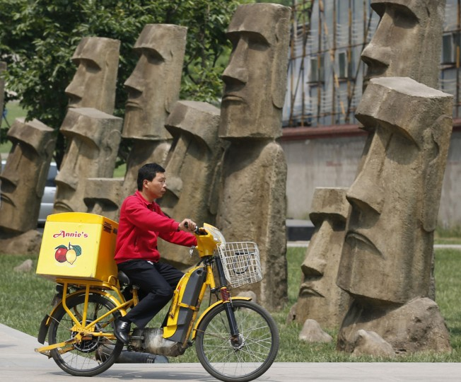 A delivery man rides past replicas of Moai statues at a business district in Beijing on May 22, 2013. (REUTERS/Kim Kyung-Hoon)