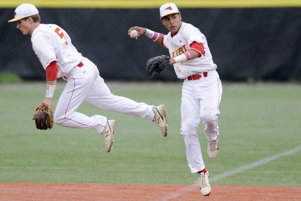 Calvert Hall shortstop Manny Rodriguez, right, throws to first after avoiding second baseman Tyler Webster during a baseball game against Mount St. Joseph on Wednesday, May 14. (Steve Ruark, Baltimore Sun Media Group)