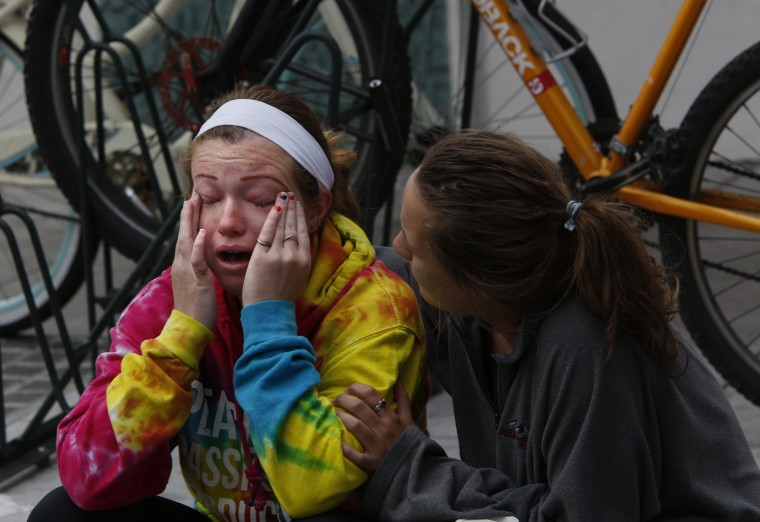 Lisa Hopper, left, is comforted by a woman she does not know, right, outside the IV Deli Mart where a man was killed as seven people including the shooter were killed last night in Isla Vista where many students attending UC Santa Barbara live on May 24, 2014. Hopper who was in the store last night when the shooting occurred dropped to the ground. She saw paramedics working on the dead man.(Anne Cusack/Los Angeles Times)