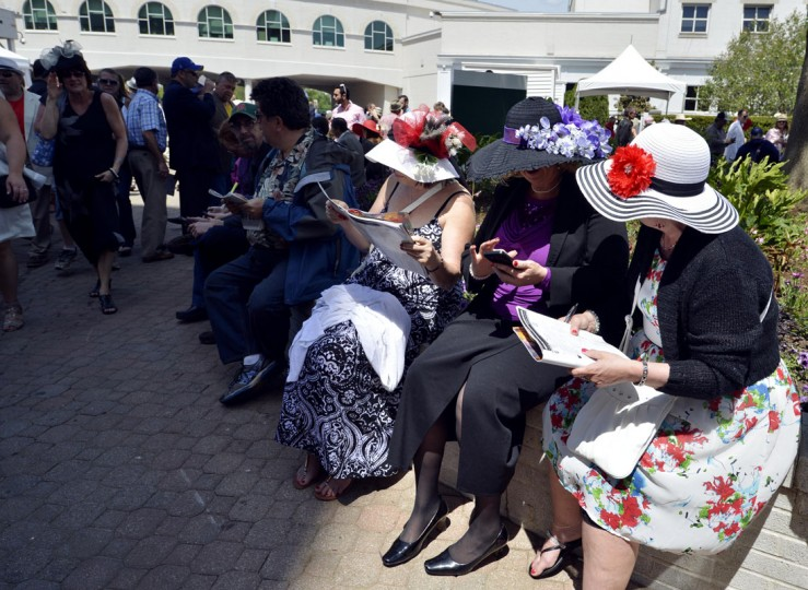 Patrons look at official programs and check messages on their phones before the 2014 Kentucky Derby at Churchill Downs. (Jamie Rhodes-USA TODAY Sports)