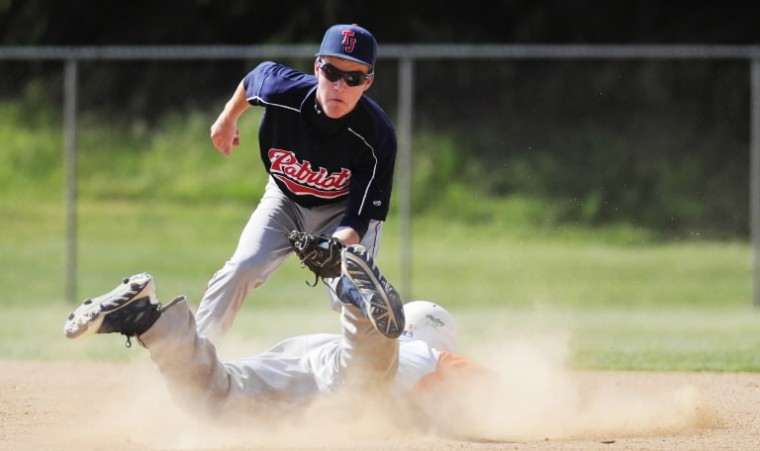 Governor Thomas Johnson second baseman Tommy Phelps reaches down with the ball in glove to make the tag on Reservoir's Danny O'Hagan during the Class 3A state semifinal baseball game at Joe Cannon Stadium. (Jon Sham/BSMG)