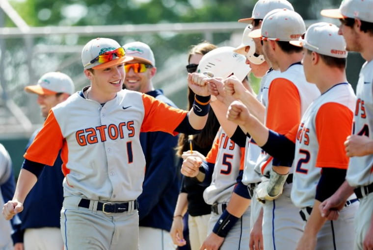 Reservoir's Joey Janush bumps fists with his teammates as he's introduced to the crowd before the Class 3A state semifinal baseball game against Governor Thomas Johnson High School at Joe Cannon Stadium in Hanover on Tuesday, May 20, 2014. (Jon Sham/BSMG)