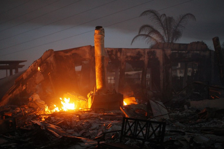 The ruins of a home smoulder in the night after it was destroyed in the Poinsettia fire, one of nine wildfires fueled by wind and record temperatures that erupted in San Diego County throughout the day, on May 14, 2014 in Carlsbad, California. Fire agencies throughout the state are scrambling to prepare for what is expected to be a dangerous year of wildfires in this third year of extreme drought in California. The Poinsettia fire has destroyed at least eight homes and severely damaged eight condos and two businesses. (Photo by David McNew/Getty Images)