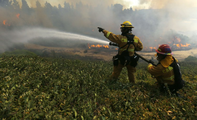 Firefighters battle fire as it turns and heads east towards another subdivision of homes in Carlsbad, California May 14, 2014. At least two structures burned to the ground and some 15,000 homes and businesses were told to evacuate on Wednesday as the wind-lashed wildfire roared out of control in the heart of a Southern California coastal community. The blaze, which erupted shortly before 11 a.m. in Carlsbad, some 25 miles north of San Diego, quickly became the most pressing battle for crews fighting flames across the region amid soaring temperatures and hot Santa Ana winds. REUTERS/Mike Blake)