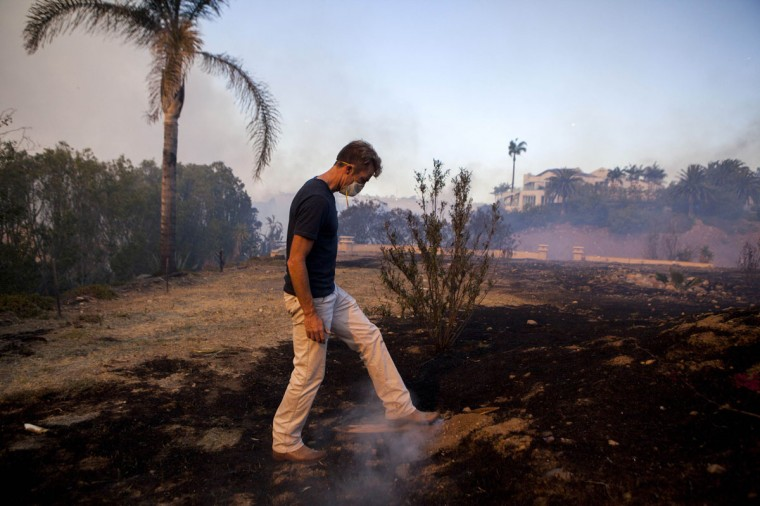 Jonathon Collopy, a resident of Fairbanks Ranch neighborhood, surveys the Bernardo Fire from a property across the street from his house near San Diego, California May 13, 2014. More than 20,000 homes and other residences were being evacuated in and around San Diego on Tuesday as a fast-moving California wildfire driven by high winds blackened more than a square mile, fire and county officials said. (REUTERS/Sam Hodgson)