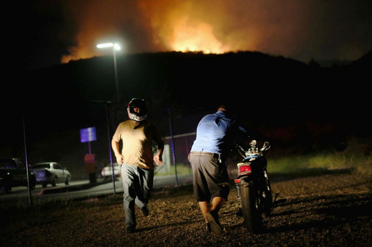 Residents move their motorcycles to safety as a fast moving wildfire approaches in San Marcos, California May 14, 2014. Wildfires roared out of control in Southern California, forcing authorities in San Diego county on Wednesday to order thousands of people to abandon their homes, including students at a state university, though no major injuries were reported. Television images showed several homes in flames, with thick black smoke filling the sky and drifting over the Pacific Ocean, as California entered the height of wildfire season in the midst of one of the state's worst droughts on record. (REUTERS/Sandy Huffaker)
