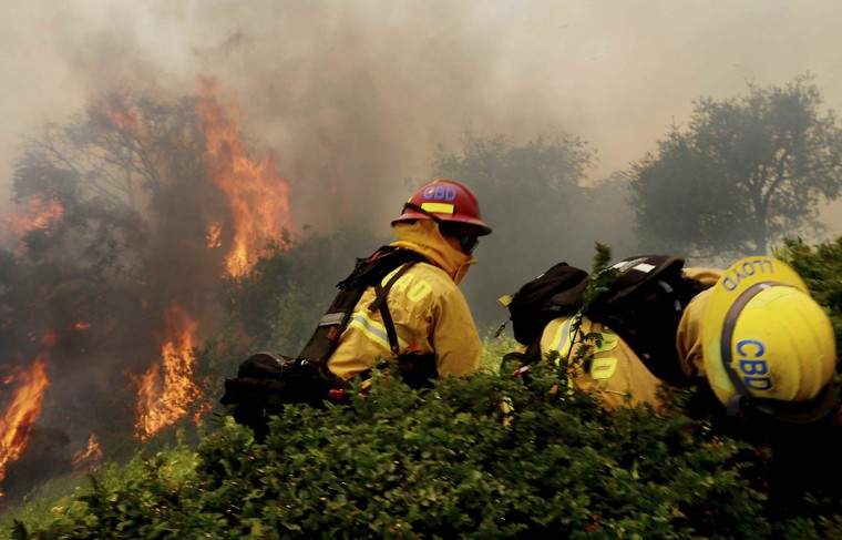 Firefighters battle a wildfire in Carlsbad, California May 14, 2014. More than 20 structures, including several homes, burned to the ground and thousands of people were ordered to evacuate on Wednesday, as a wind-lashed wildfire roared out of control in the heart of the Southern California coastal community of Carlsbad. (REUTERS/Sandy Huffaker)