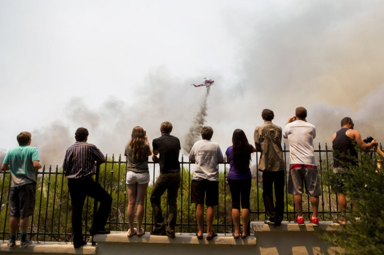 Residents watch firefighters battle the so-called Poinsettia Fire in Carlsbad, California May 14, 2014. At least two structures burned to the ground and some 15,000 homes and businesses were told to evacuate on Wednesday as the wind-lashed wildfire roared out of control in the heart of a Southern California coastal community. The blaze, which erupted shortly before 11 a.m. in Carlsbad, some 25 miles north of San Diego, quickly became the most pressing battle for crews fighting flames across the region amid soaring temperatures and hot Santa Ana winds. (REUTERS/Sam Hodgson)