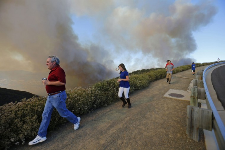 After climbing a hillside to view the so-called Poinsettia Fire, residents are evacuated by police as yet another wildfire near San Diego moves up a hillside near San Marcos, California May 14, 2014. At least two structures burned to the ground and some 15,000 homes and businesses were told to evacuate on Wednesday as the wind-lashed Poinsettia wildfire roared out of control in the heart of a Southern California coastal community. The blaze, which erupted shortly before 11 a.m. in Carlsbad, some 25 miles north of San Diego, quickly became the most pressing battle for crews fighting flames across the region amid soaring temperatures and hot Santa Ana winds. (REUTERS/Mike Blake)