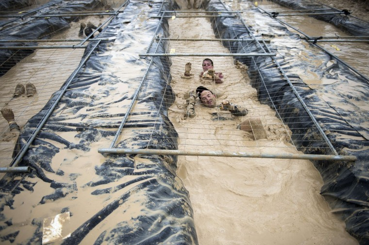 "Runners take part in ""The Mud Day challenge"", a 13-kilometer obstacles course in Beynes near Paris, France. (Martin Bureau/AFP-Getty Images)"