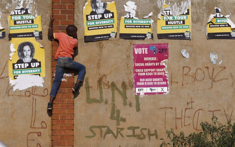 A child climbs past defaced election posters during an election rally of President Jacob Zuma's African National Congress (ANC) in Bekkersdal township south of Johannesburg. South Africa goes to the polls on May 7 in elections which are expected to keep the ANC in power. (Mitch Hutchings/Reuters)