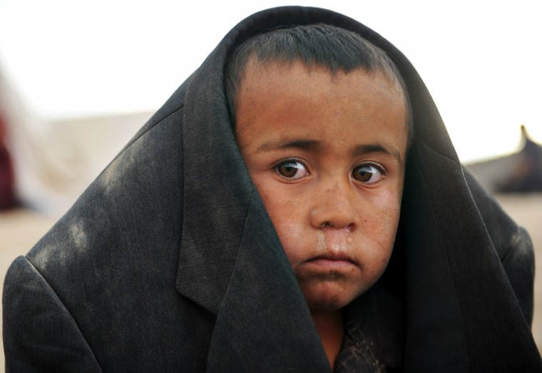 An Afghan boy at the site of a landslide at the Argo district in Badakhshan. A landslides buried a village in northern Afghanistan on Friday, killing at least 350 people and leaving thousands of others feared dead, as rescuers searched desperately for survivors trapped under the mud. Villagers at the disaster site in Badakhshan province used shovels to dig through rocks and dirt, with national authorities, the United Nations and the US-led military force all racing to assess the damage and provide help.(Farshad Usyan/AFP-Getty Images)