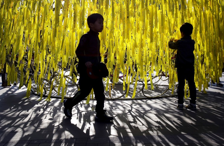 A boy ties a yellow ribbon of hope for the safe return of missing passengers and in tribute to the victims of the sunken ferry Sewol in Seoul, South Korea. On April 16 the Sewol ferry carrying 476 passengers sunk off the island of Jindo. More than 302 passengers are dead or missing and the cause of the accident is still under investigation. (Chung Sung-Jun/Getty Images)