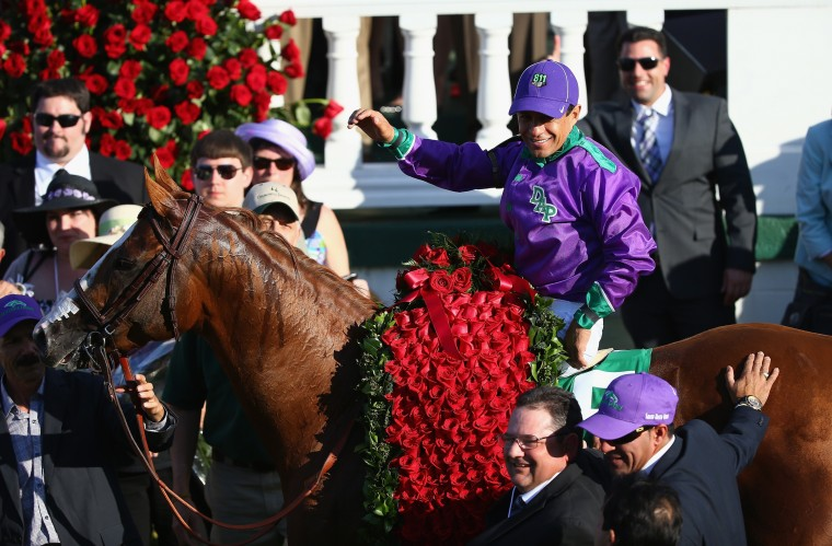 Victor Espinoza celebrates in the winners circle after riding California Chrome (5) to victory in the 140th running of the Kentucky Derby at Churchill Downs in Louisville, Ky. (Andy Lyons/Getty Images)