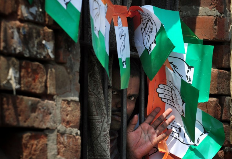 A resident of a neighborhood in Varanasi looks through a window of his house adorned with Congress party political leaflets as he waits for a procession by India's Congress Party Vice President Rahul Gandhito go past his house on the final day of campaigning in the Indian elections. India's 814-million-strong electorate is voting in the world's biggest election which is set to sweep the Hindu nationalist opposition to power at a time of low growth, anger about corruption and warnings about religious unrest. (Roberto Schmidt/AFP-Getty Images)