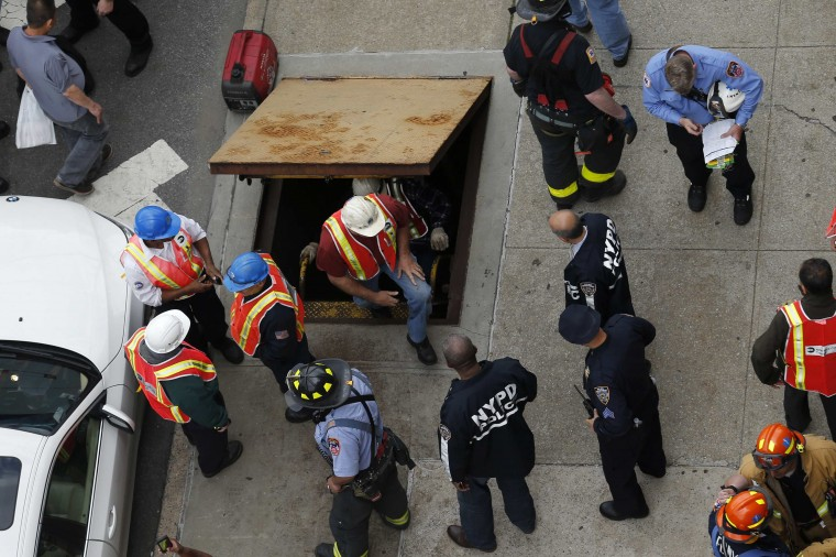 Metropolitan Transportation Authority (MTA) workers exit an emergency staircase after evacuating from a derailed F train in Woodside, N.Y. The New York City subway train carrying 1,000 riders derailed on Friday morning while traveling through a tunnel in the borough of Queens, injuring 19 people, city fire officials said. Fifteen people escaped with minor injuries while four more were transported to a hospital with potentially serious injuries, officials said. (Eduardo Munoz/Reuters)