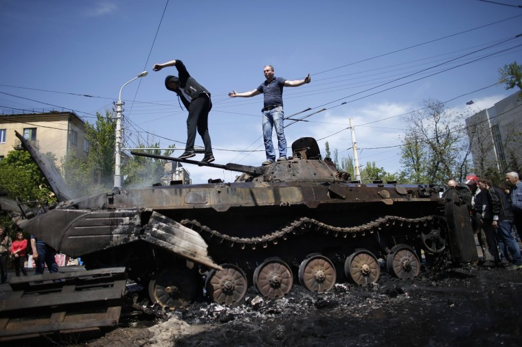 People stand on top of burnt-out armored personal carrier near the city hall in Mariupol, eastern Ukraine. At least seven people were killed and dozens wounded in clashes in the port city on Friday, two days before a referendum on self-rule that threatens to plunge the country into civil war. (Marko Djurica/Reuters)
