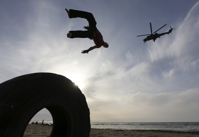 A Libyan man practices parkour, as a helicopter flies past, at the beach in Benghazi. (Esam Omran Al-Fetori/Reuters)