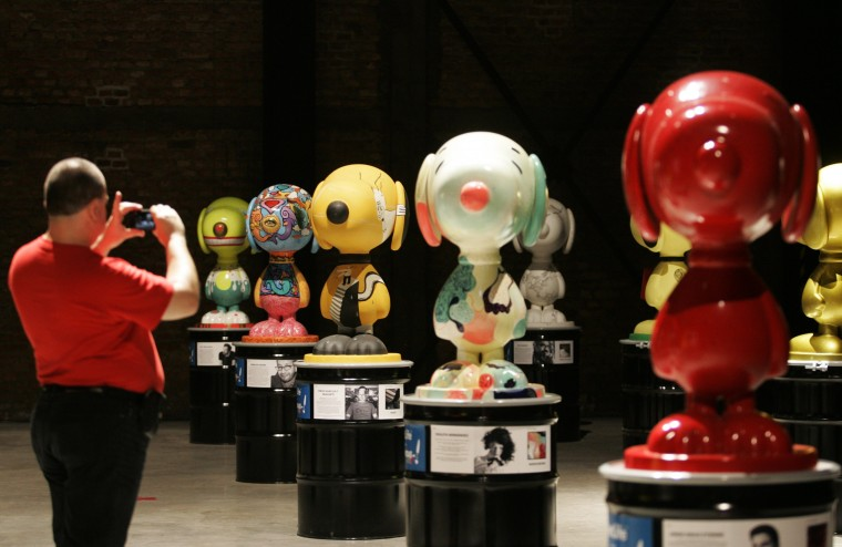 """A visitor photographs Snoopy sculptures created by Mexican artists and on display during the """"Snoopy visits Guadalajara"""" event at a gallery in Mexico. The event is part of a charity initiative to support women from Chiapas and their culture, which will run until May 17. (Alejandro Acosta/Reuters)"""