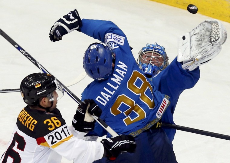 Kazakhstan's goalie Vitali Yeremeyev and Kevin Dallman try to catch the puck in front of Germany's Yannic Seidenberg (left) during the third period of their men's ice hockey World Championship Group B game at Minsk Arena in Minsk. (Alexander Demianchuk/Reuters)