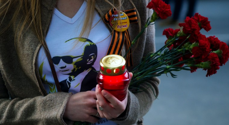 A woman wears a t-shirt with a portrait of Russian President Vladimir Putin as she holds a candle near the Ukrainian embassy in Moscow during a commemoration in honor of people killed during clashes in Odessa. Ukrainian soldiers and pro-Russian rebels fought fierce battles today around a flashpoint town, with only a small reprieve to allow passage of a freed team of OSCE inspectors. More than 50 people have died in two days of clashes nationwide -- most of them in a horrific inferno amid street clashes in the southern city of Odessa. (Anatoly Tanin/AFP-Getty Images)