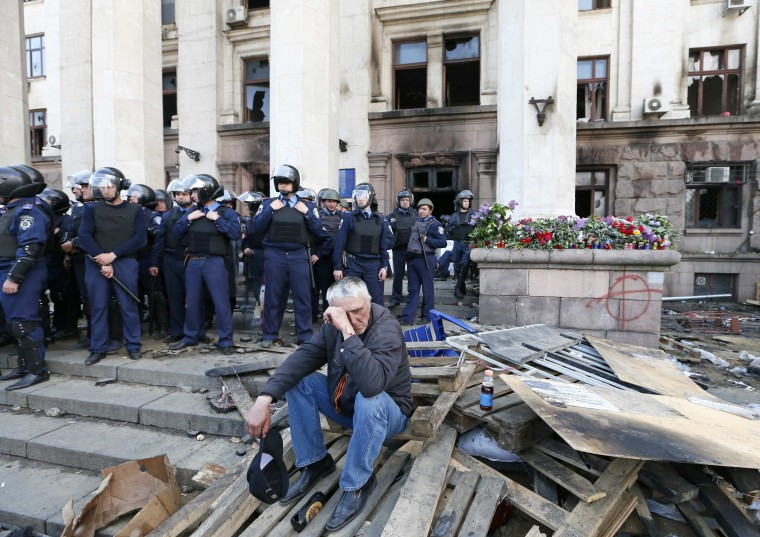 A man, wearing a black and orange ribbon of St. George, a symbol widely associated with pro-Russian protests in Ukraine, reacts outside a trade union building, where a deadly fire occurred, with Ukrainian Interior Ministry security forces members seen in the background, in Odessa, May 3, 2014. At least 42 people were killed in street battles between supporters and opponents of Russia in southern Ukraine that ended with pro-Russian protesters trapped in a flaming building, bringing the country closer to war. The riot in the Black Sea port of Odessa that ended in a deadly blaze in a trade union building was by far the worst incident in Ukraine since a February uprising that ended with a pro-Russian president fleeing the country. (Gleb Garanich/Reuters)