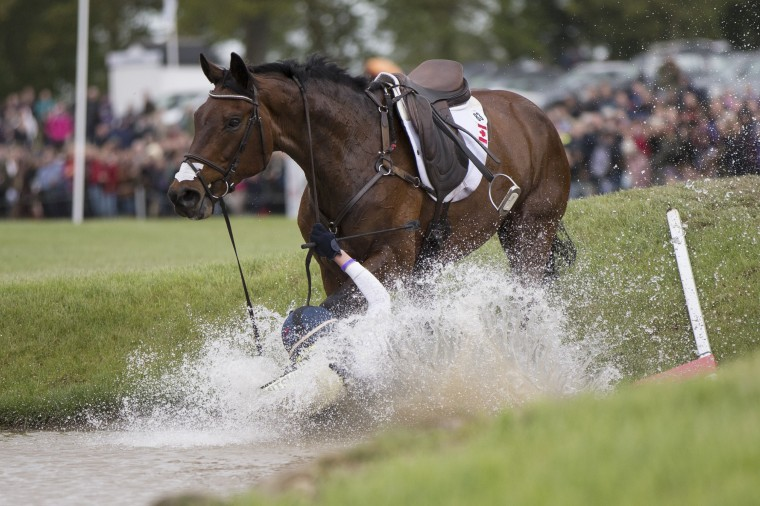 Canadian rider Rebecca Howard falls from her horse 'Riddle Master' at the Mirage Pond jump of the Cross County discipline on the penultimate day of the Badminton Horse Trials in Badminton, England. The Badminton Horse Trials, which were first held in1949, take place over 6 days on the Duke of Beaufort's Badminton Estate. (Oli Scarff/Getty Images)