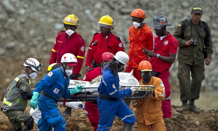 Colombian rescuers carry the corpse of one of the victims of a gold mine that collapsed --on May 1st-- while independent mine workers were excavating it without authorization, in San Antonio, rural area of Santander de Quilichao, department of Cauca, Colombia. Rescue workers recovered the body of a fourth miner killed in the landslide, leaving a dozen others still unaccounted for. (Luis Robayo/AFP-Getty Images)