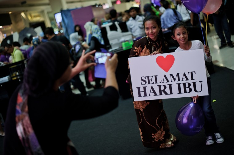 "A mother (L) takes pictures of her daughters holding a placard reading ""Happy Mother's Day"" at a shopping mall in Kuala Lumpur. Mothers Day is celebrated around the world though on different dates. (Mohd Rasfan/AFP-Getty Images)"