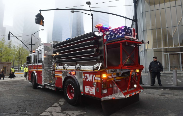 A casket carrying the unidentified remains of victims of the September 11, 2001 attacks sits atop a firetruck as the remains are escorted to a repository at Ground Zero in New York. Three caskets with remains were moved from the medical examiner's office to a repository built under the National September 11 Memorial and Museum at the World Trade Center site. (Emmanuel Dunand/AFP-Getty Images)