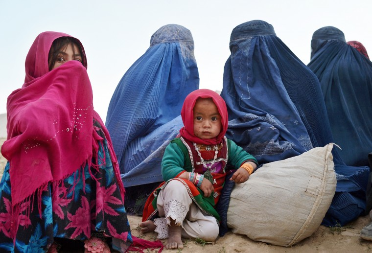 Afghan villagers look on at the scene in Argo district of Badakhshan province after a massive landslide May 2 buried a village. Rescue teams abandoned the search for survivors May 3 after a landslide buried a hillside village in northern Afghanistan, killing at least 300 people under a fast-moving tide of rock and mud. (Shah Marai/AFP-Getty Images)
