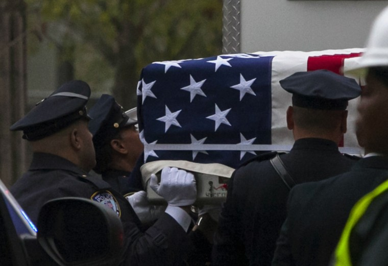 Emergency personnel carry a casket draped with a U.S. flag during the ceremonial transfer of the 9/11 unidentified remains to the Office of the Chief Medical Examiner of the City of New York (OCME) repository at the World Trade Center site, in New York. According to local media, relatives of victims of the September 11 attacks, who are incensed with the city over its plan to house the remains underground in the same building as the National September 11 Memorial Museum, held a protest on the day of the transfer of the remains. The protesters left shortly before the ceremony began. (Eric Thayer/Reuters)
