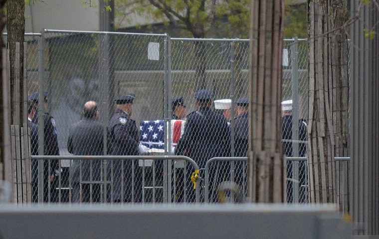 A casket carrying the unidentified remains of victims of the September 11, 2001 attacks are escorted to a repository at Ground Zero in New York. The unidentified remains were moved from the medical examiner's office to a repository built under the National September 11 Memorial and Museum at the World Trade Center site. (Emmanuel Dunand/AFP-Getty Images)