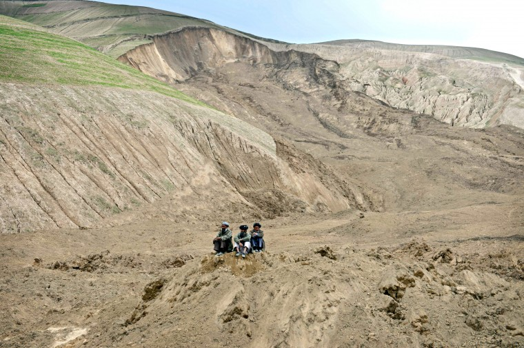Afghan villagers look on at the scene in Argo district of Badakhshan province after a massive landslide May 2 buried a village. Rescuers searched in vain for survivors May 3 after a landslide buried an Afghan village, killing 350 people and leaving thousands of others feared dead amid warnings that more earth could sweep down the hillside. Local people made desperate efforts to find victims trapped under a massive river of mud that engulfed Aab Bareek village in Badakhshan province, where little sign remained of hundreds of destroyed homes. (Shah Marai/AFP-Getty Images)