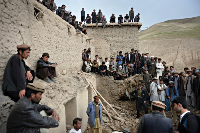 Afghan villagers look on as rescuers search desperately for survivors trapped under the mud in Argo district of Badakhshan province on after a massive landslide May 2 buried a village. Rescuers searched in vain for survivors May 3 after a landslide buried an Afghan village, killing 350 people and leaving thousands of others feared dead amid warnings that more earth could sweep down the hillside. Local people made desperate efforts to find victims trapped under a massive river of mud that engulfed Aab Bareek village in Badakhshan province, where little sign remained of hundreds of destroyed homes. (Shah Marai/AFP-Getty Images)