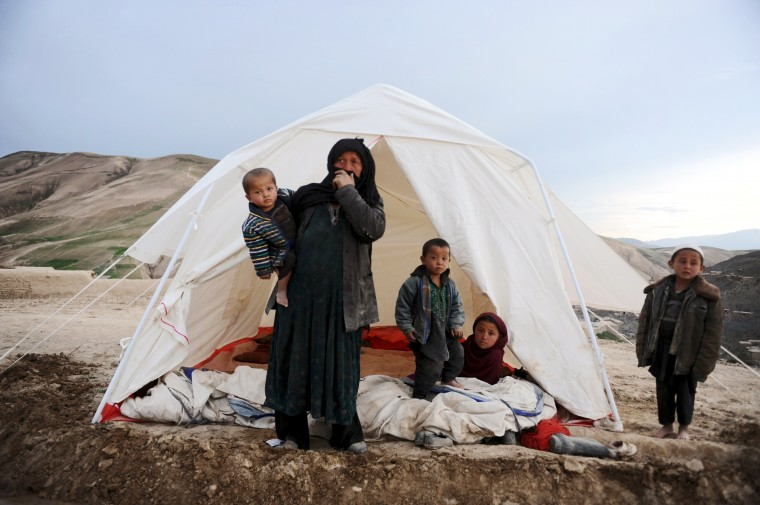 An Afghan woman with her children stands near her tent at the site of a landslide at the Argo district in Badakhshan. A landslides buried a village in northern Afghanistan on Friday, killing at least 350 people and leaving thousands of others feared dead, as rescuers searched desperately for survivors trapped under the mud. Villagers at the disaster site in Badakhshan province used shovels to dig through rocks and dirt, with national authorities, the United Nations and the US-led military force all racing to assess the damage and provide help.(Farshad Usyan/AFP-Getty Images)